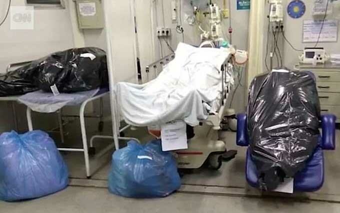 Bệnh nhân nằm cạnh hai túi đựng thi thể tại bệnh viện ở Rio de Janeiro. Ảnh: CNN.