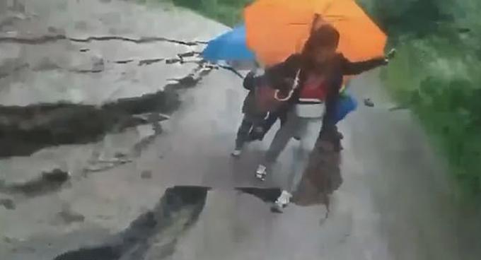 Ba mẹ con ở Carpathian nhảy qua đoạn đường sụt lún do lũ lụt hôm 23/6. Ảnh: CEN.