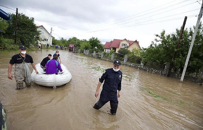 Lực lượng cứu hộ giải cứu người dân ra khỏi vùng lụt ở Ukraine hôm 24/6. Ảnh: PA.
