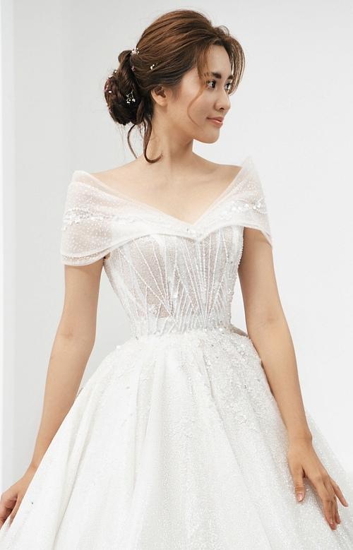 Kiểu cổ trễ vai có nhiều ưu điểm khi vừa tôn được nét điệu đà, e lệ vừa khéo che phần bắp tay to của cô dâu.