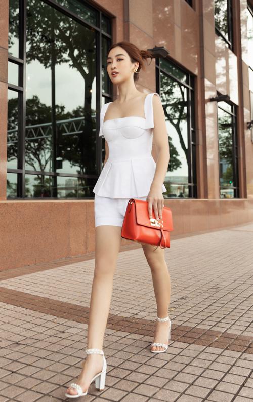 Thay vì sử dụng các mẫu túi xách tay, clutch trắng như các fashionista, Đỗ Mỹ Linh chọn phụ kiện tông màu nổi để tạo điểm nhấn.