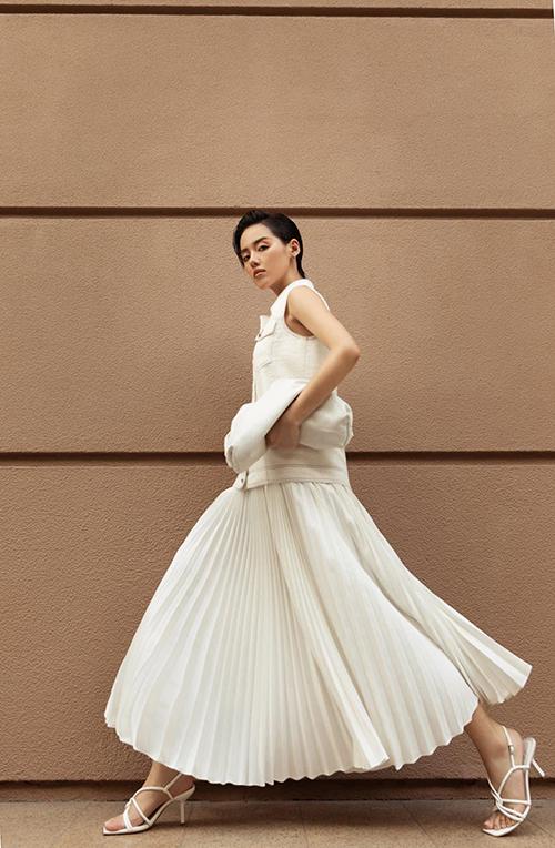 Vẫn áp dụng công thức phối đồ tiệp sắc trắng, Khánh Linh giúp hình ảnh của cô trở nên cuốn hút hơn với thiết kế váy dập ly đúng trend 2020.