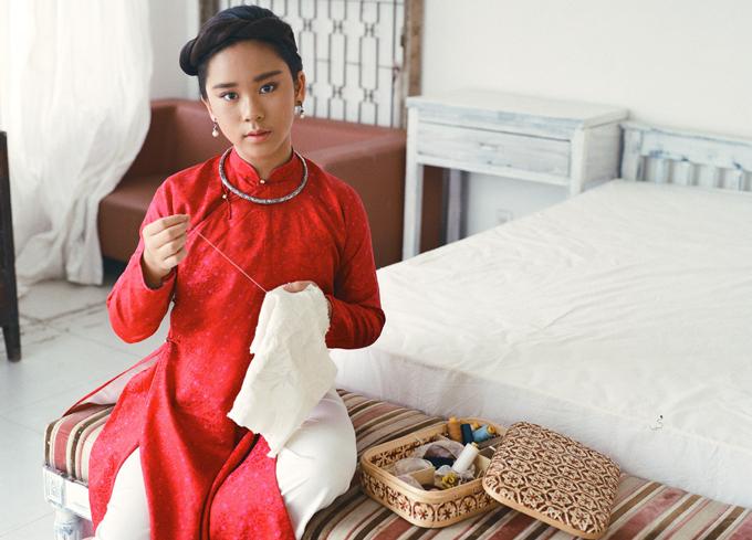 Mẫu nhí hóa thân thiếu nữ thời xưa với áo dài đỏ, kiềng bạc, khăn vấn đang ngồi khâu vá, thêu thùa.