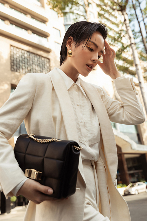 Ngoài cách phối hợp phụ kiện ton-sur-ton với trang phục, Khánh Linh chọn thêm túi xách màu tương phản khi diện nguyên set trang phục trắng.
