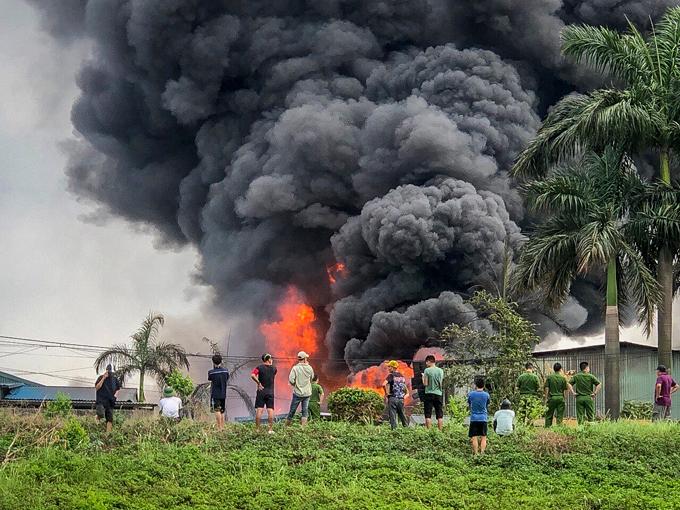 Lửa bùng lên dữ dội kèm theo những cột khói đen cuồn cuộn tại kho nhà xưởng hóa chất ở Long Biên. Ảnh: Phạm Chiểu.
