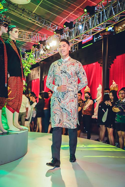 Là gương mặt đầu tiên bước ra sân khấu, Justin Young diện bộ áo dài in họa tiết hoa lá. Đây là đêm diễn thuộc khuôn khổ Triển lãm hơn một thế kỷ áo dài diễn ra tại phố đi bộ Nguyễn Huệ (quận 1, TP HCM) từ ngày 27/6 - 2/7).