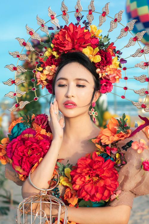 NTK Phạm Đăng Anh Thư chia sẻ về tác phẩm của mình: Mina diện váy xòe bồng có nền màu nude ẩn ánh đồng. Những dải hoa dây leo hiệu ứng 3D dọc thân cùng những mảng hoa lá màu sắc rực rỡ theo bảng màu rừng nhiệt đới là điểm nhấn đặc sắc của bộ cánh. Những đóa hoa bung tỏa với các tông màu đối nghịch, tạo sự tương phản thị giác mạnh mẽ trên bộ váy voan tơ, mang đến nhịp điệu sôi động của ngày hè. Mina Phạm kết hợp bộ cánh với vương miện mạ vàng kết hoa tạo nên tổng thể ấn tượng.