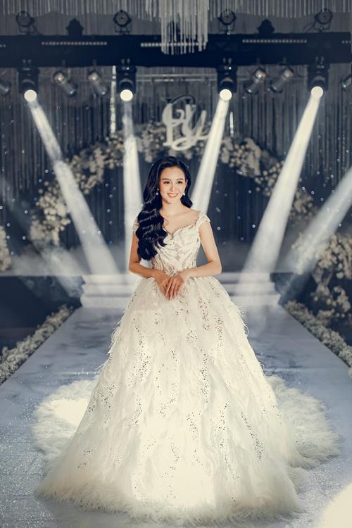 Hải Yến thay ba bộ váy cưới của NTK Lâm Lâm trong chính tiệc. Riêng bộ này, NTK dùng hơn 20.000 viên đá swarovski kích thước khác nhau cùng phần họa tiết kết lông vũ và hạt cườm được đính tay cầu kỳ.