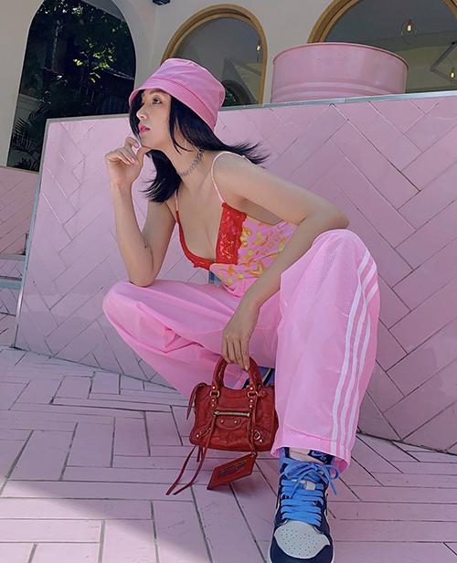 Sĩ Thanh nổi bật trên phố với cách phối hợp hai tông màu đỏ và hồng với áo hai dây, quần thể thao và túi mini của Balenciaga.