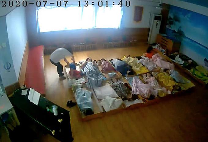 Một em bé bị xốc nách đưa ra góc riêng trừng trị vì không ngủ trưa ở nhà trẻ tại Ninh Ba, Chiết Giang, Trung Quốc hôm 7/7. Ảnh cắt từ video.