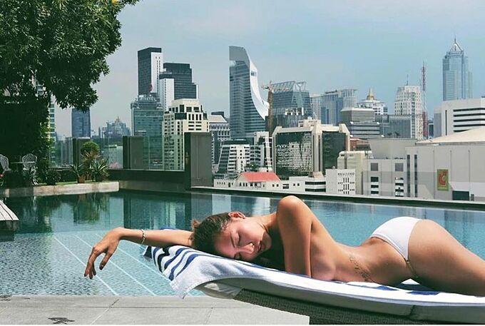 Người mẫu Minh Triệu bán nút tắm nắng khi nằm thư giãn bên hồ bơi.