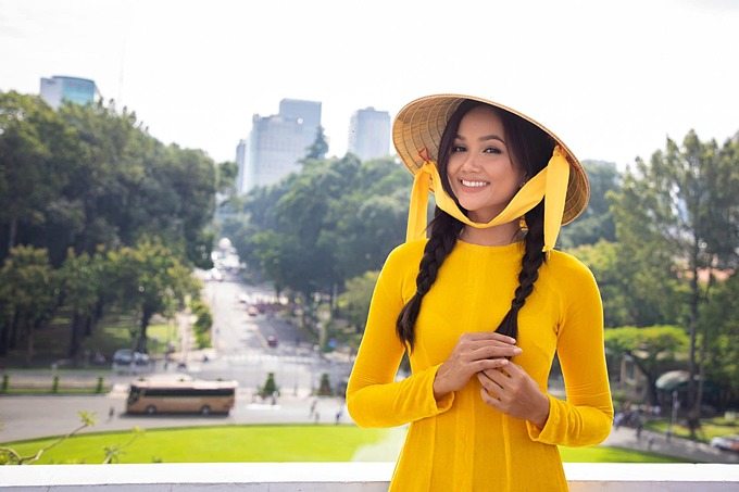HHen Niê hóa thôn nữ với áo bà ba, nón lá và tóc dài tết hai bên.