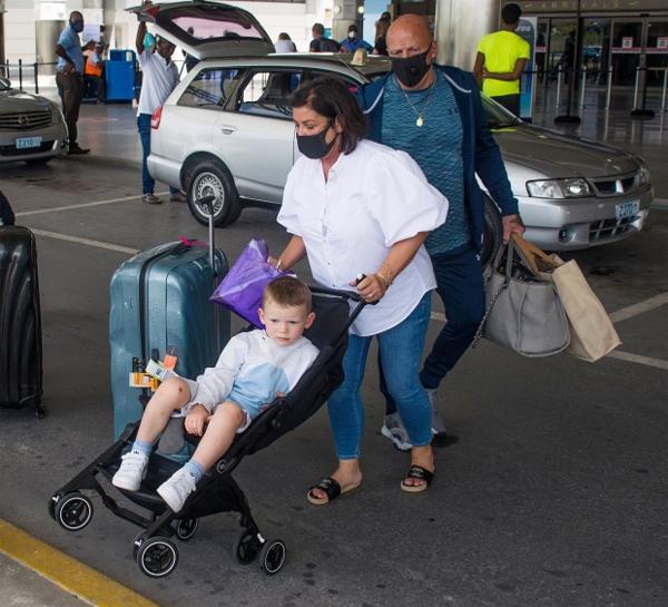 Mẹ Coleen đẩy xe chở cậu con trai thứ ba của cặp đôi - bé Kit - trong khi bố cô xách hành lý đi phía sau.