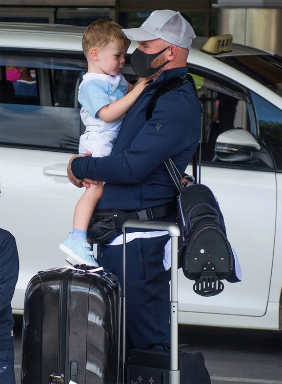 Rooney đeo khẩu trang bế bé út Cass tại sân bay.