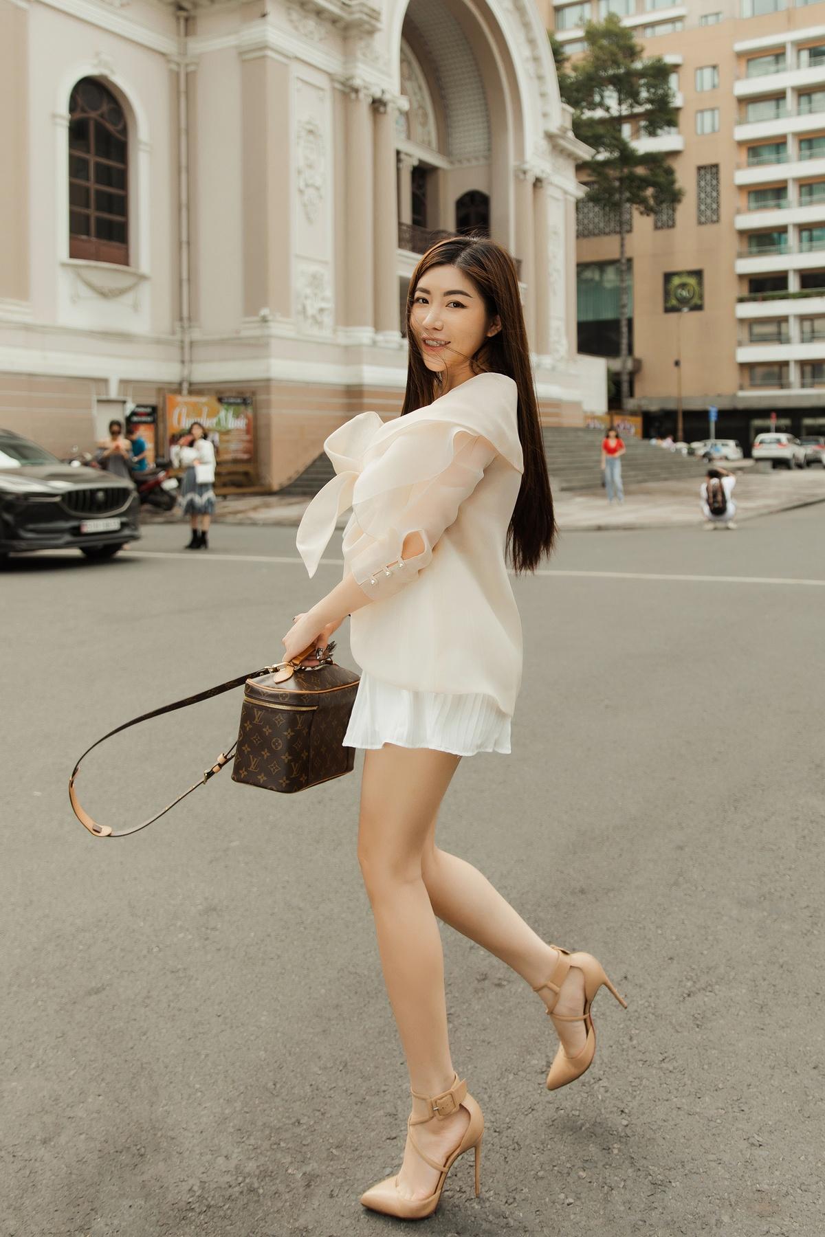 Với phong cách thanh nhã hơn, Amanda Baby chọn chiếc áo có thiết kế nơ to bằng chất liệu vải lụa dệt lưới, mang đến cảm giác mát nhẹ, kết hợp cùng chân váy ngắn để khoe đôi chân thon dài.