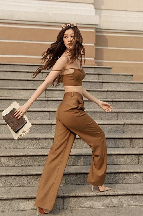 Phong cách sexy với mốt khoe eo thon được Khánh Vân thể hiện cuốn hút với bộ trang phục được kết hợp giữa áo hai dây và quần suông ống đứng.