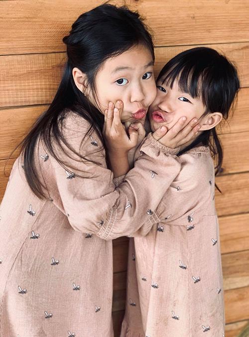Hai chị em Cherry (trái) và Sunny được mẹ cho mặc váy đồng phục điệu đà. Sunny tính hiếu động, hay cười còn Cherry được nhận xét ra dáng người lớn so với tuổi.
