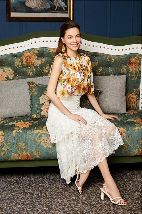 Váy ren xếp tầng trắng tinh khiến họa tiết hoa hướng dương trên chiếc áo voan không tay trở nên nổi bật.