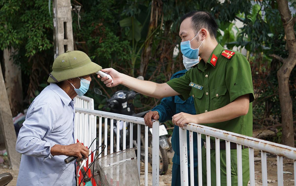 Một cụ ông được cảnh sát đo thân nhiệt trước khi vào phố Nam Bắc. Ảnh: Lê Hoàng.