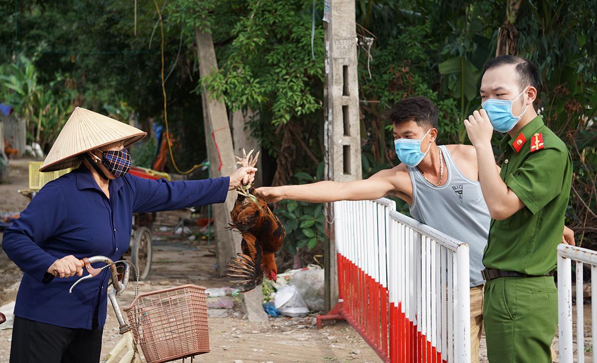 Một người dân nhận thực phẩm từ người thân tại chốt kiểm soát đầu phố Nam Bắc, phường Quảng Vinh chiều 6/8. Ảnh: Lê Hoàng.
