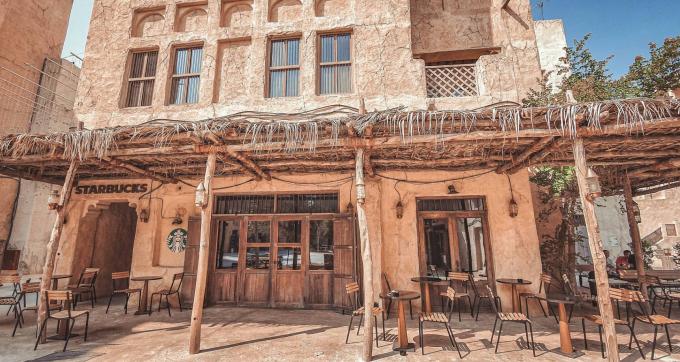 Cửa tiệm tận dụng hành lang làm khu ngoài trời cho khách ngồi hóng gió. Bàn ghế theo kiểu đơn giản. Ngoài logo nhãn hiệu mang hơi hướng hiện đại ra, mọi thứ đều đậm chất Trung Đông như tường màu đặc trưng của cát sa mạc hay mái che bằng lá cây...