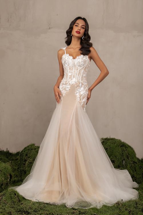 Đầm trumpet trắng pha cam nhạt là gợi ý giúp tôn vẻ quyến rũ của tân nương, lựa chọn phù hợp để cô dâu chào bàn. Đầm được đắp ren, dựng gọng để định hình, tôn dáng vóc tối đa.