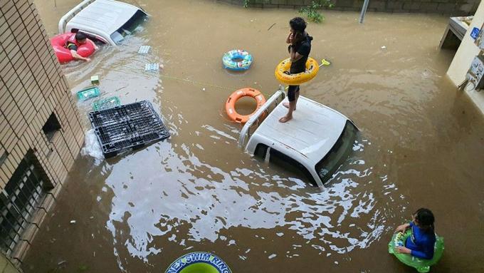 Một người đàn ông đứng trên nóc xe ôtô bị ngập chờ đuọc giải cứu ở Hadong, Hàn Quốc. Ảnh: Sky News.