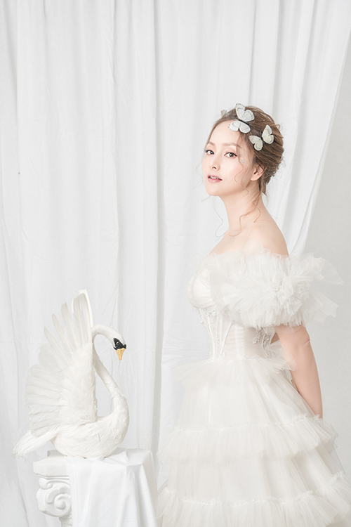 Nữ diễn viên như hóa thành vũ công bale với váy trắng tinh khôi. Bộ cánh được dựng gọng giúp định hình thân trên, có tác dụng nâng đẩy ngực tối đa.