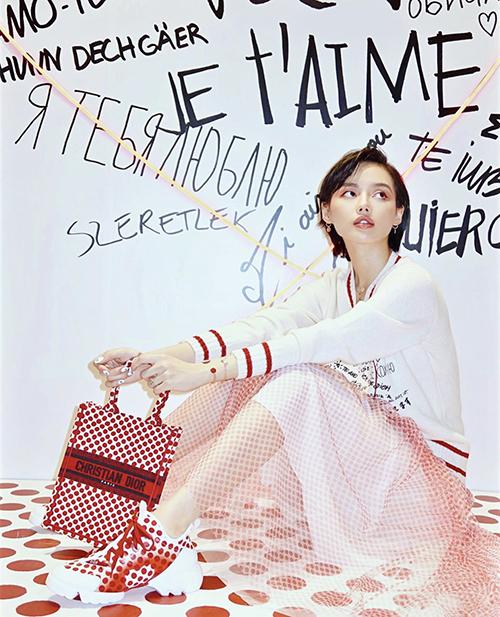 Túi Dior với hoạ tiết chấm bi xinh xắn được Khánh Linh phối hợp nhịp nhàng cùng giày thể thao, chân váy tuyn và áo len mỏng.