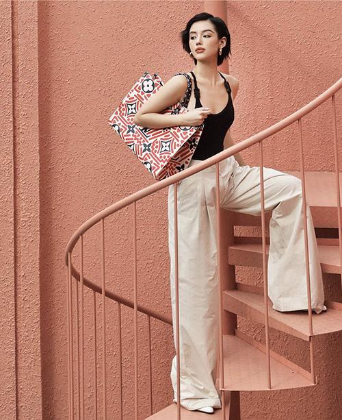 Túi to bản trang trí hoa văn và logo hàng hiệu được Khánh Linh sử dụng cùng mẫu áo hai dây ôm body và quần ống suông hack dáng.