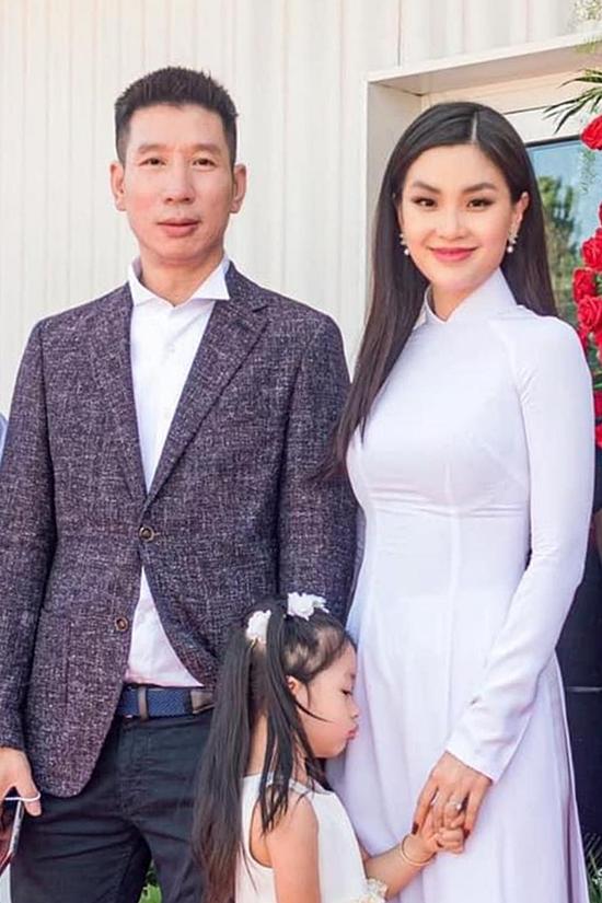 Diễm Trang diện áo dài trắng bên cạnh chồng con trong buổi lễ khai trương cách đây ít hôm.