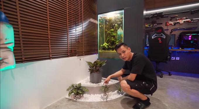 Là người mạng Mộc, Độ Mixi đem vào không gian làm việc ít cây xanh, rải thêm sỏi trắng để che đất. Anh chọn các cây phù hợp sống trong nhà, ít cần chăm sóc. Bên cạnh là bể cá cảnh giúp Độ Mixi thư giãn sau các giờ livestream.