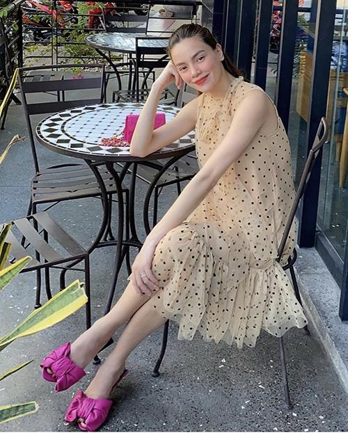 Đầm chấm bi của Hồ Ngọc Hà được trang trí dây nơ và phần hạ eo xếp bèo duyên dáng. Nữ ca sĩ chọn nguyên bộ phụ kiện hồng cánh sen để phối đồ khi đi cafe.
