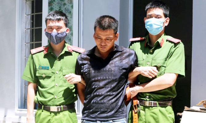Nghi can Thành (giữa) bị cảnh sát khống chế. Ảnh: C.A