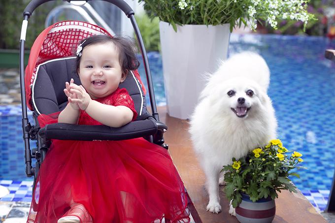 Cô bé thoải mái nô đùa, cười khúc khích khi tạo dáng cùng các chú cún cưng bên bể bơi của nhà.