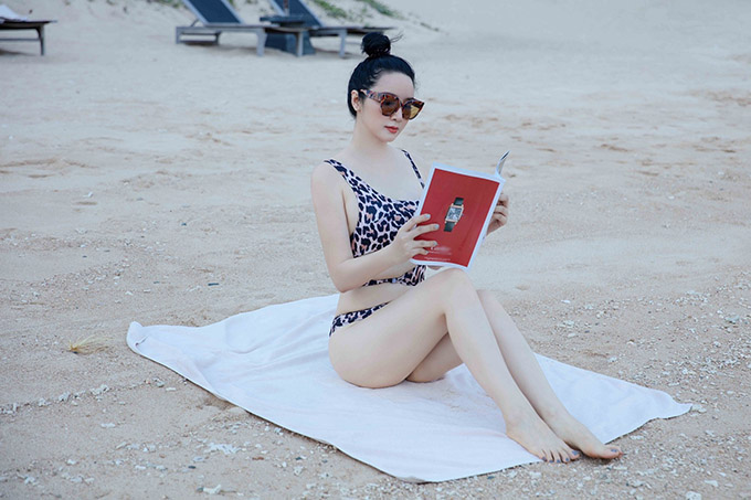 Mỹ nhân 7X vừa phơi nắng vừa đọc báo trên bãi biển vắng người.