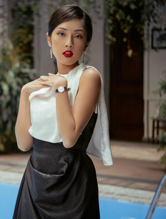 Người đẹp duyên dáng, trẻ trung với kiểu tóc buộc cao, váy áo hai màu đen trắng đơn giản, kín đáo.