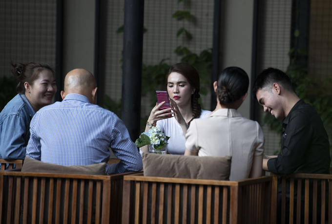 Người đẹp đến sớm, tranh thủ đọc báo, lướt mạng trong khi chờ các đối tác khác.
