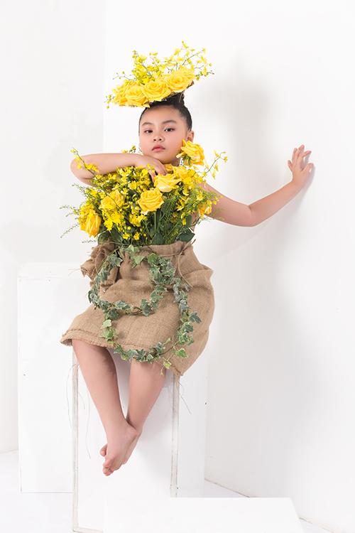 Mẫu nhí nổi bật với thiết kế váy hoa hồng vàng, chân váy dược tạo bởi bao bố, dây thừng dáng mảnh.