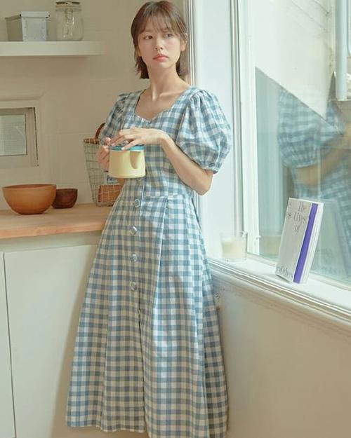 Váy cài nút điệu đà cho các nàng mê dòng thời trang vintage. Kết hợp cùng kiểu đầm vai bồng là hoạ tiết ca rô phối màu xanh - trắng tạo nên sự thanh nhã.