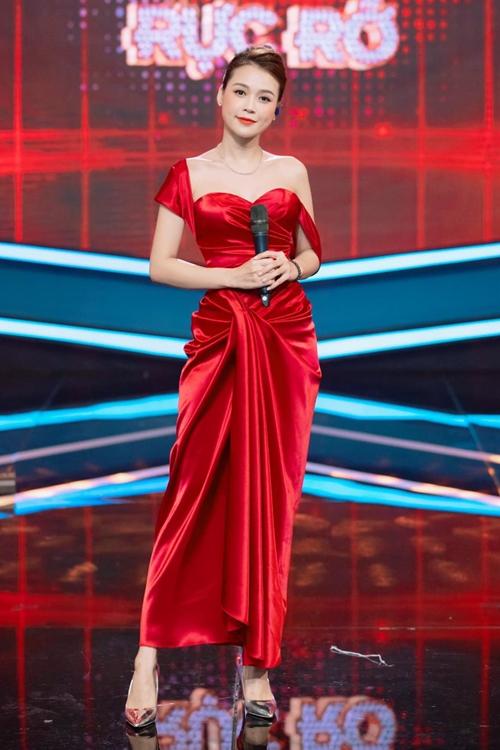 Đầm đỏ với chất liệu lụa satin và phần vạt bất đối xứng mang đến vẻ duyên dáng, kiêu sa cho nữ MC. Mặc bộ đồ này, Sam không ngại đụng hàng với hoa hậu Đỗ Mỹ Linh, hoa hậu Khánh Vân và nữ hoàng nội y Ngọc Trinh.