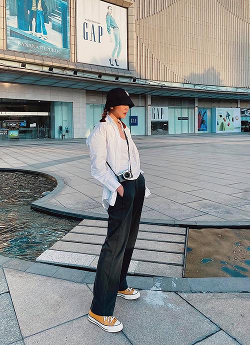 Thanh Hằng hack tuổi khi làm tóc thắt bím hai bên, đội mũ rộng vành và mix sơ mi cùng quần suông, giày đế bệt trẻ trung.
