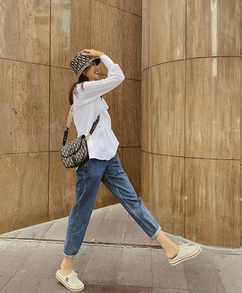 Sơ mi trắng nhiều kiểu dáng được Thanh Hằng thường phối cùng các mẫu jeans tiện lợi khi dạo phố. Khi mix những món đồ đơn giản, đệ nhất chân dài của lãng mẫu không quên chọn phụ kiện hàng hiệu đúng trend để tạo điểm nhấn.