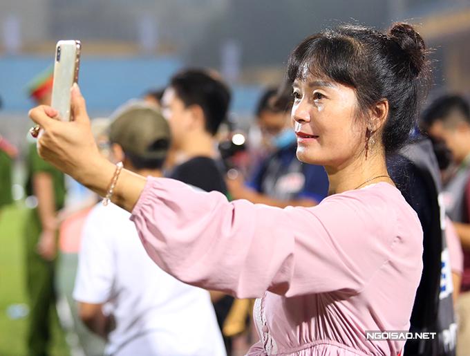 Bà Nguyễn Ánh Tuyết - mẹ trung vệ Thành Chung đứng từ xa quay lại cảnh con trai ăn mừng cùng các đồng đội.