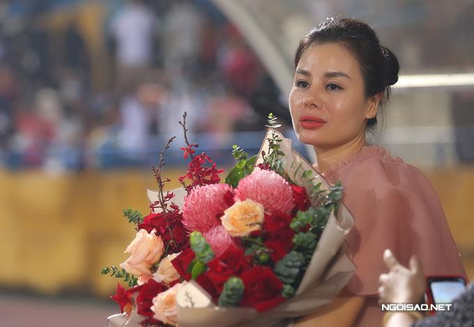Bà xã Lệ Quyên mang hoa xuống sân tặng và khích lệ HLV Trương Việt Hoàng.