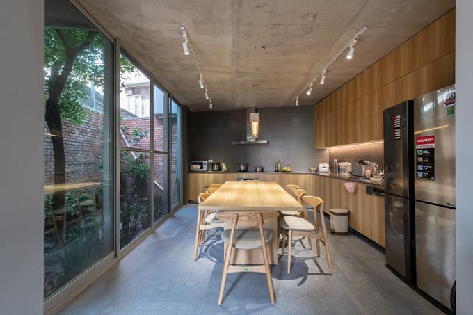 Nhà bếp và phòng khách thông với không gian sinh hoạt chung cho cả gia đình. Chủ nhà là một người yêu thiên nhiên nên đã đặc biệt thiết kế riêng một giếng trời để trồng cây, mang sự xanh mát vào ngôi nhà của mình. Điểm nhấn thuộc về căn bếp đầy đủ tiện nghi. Tủ bếp chữ L và bàn ăn đều được làm từ chất liệu gỗ công nghiệp có độ bền cao, bề mặt vân gỗ bóng mịn.