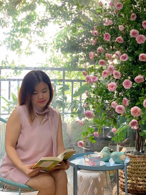 Lan Phương đọc sách bên cây hoa hồng của mình. Cô bổ sung: Mỗi ngày tôi sẽ phun nước dạng sương vào cành lá hoa, xốp tới khi đủ ướt lá với tần suất 2-3 lần. Chịu khó cắt, nhặt nhạnh cành lá héo úa, chỉnh một số cành đã héo, rụng để đảm bảo thẩm mỹ.