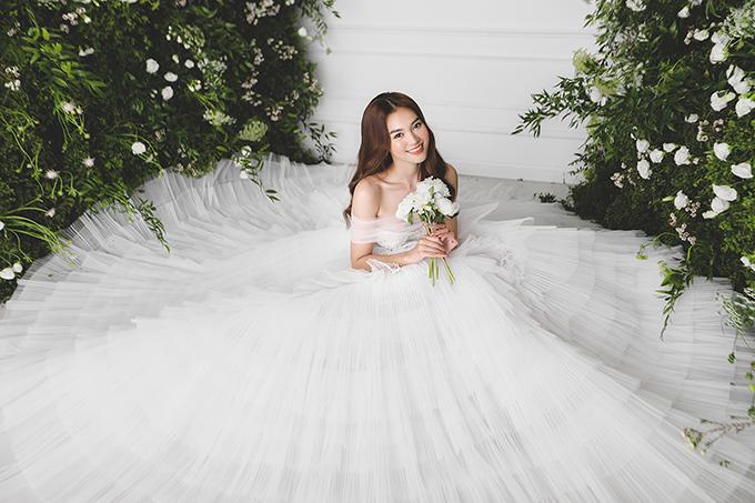 Bộ váy cưới trễ vai với tùng váy bồng xoè xếp ly mềm mại từ chất liệu voan cao cấp.