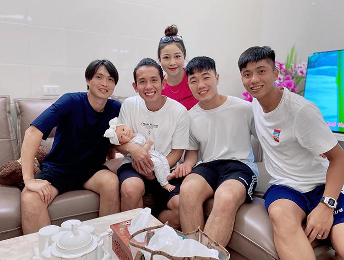 Các cầu thủ HAGL chụp ảnh cùng vợ chồng và con gái Văn Đức trong buổi tới thăm nhà. Ảnh: VNL.
