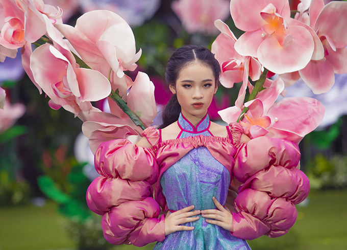 Mẫu 11 tuổi ấn tượng với trang phục lấy cảm hứng từ hoa lan. Đây là thiết kế đòi hỏi người mẫu nhí phải có những bước đi vững, khả năng giữ cân bằng tốt để không gặp sự cố trong khi trình diễn.